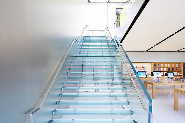 Two glass stairs lead to the upper floor of the Apple Store.