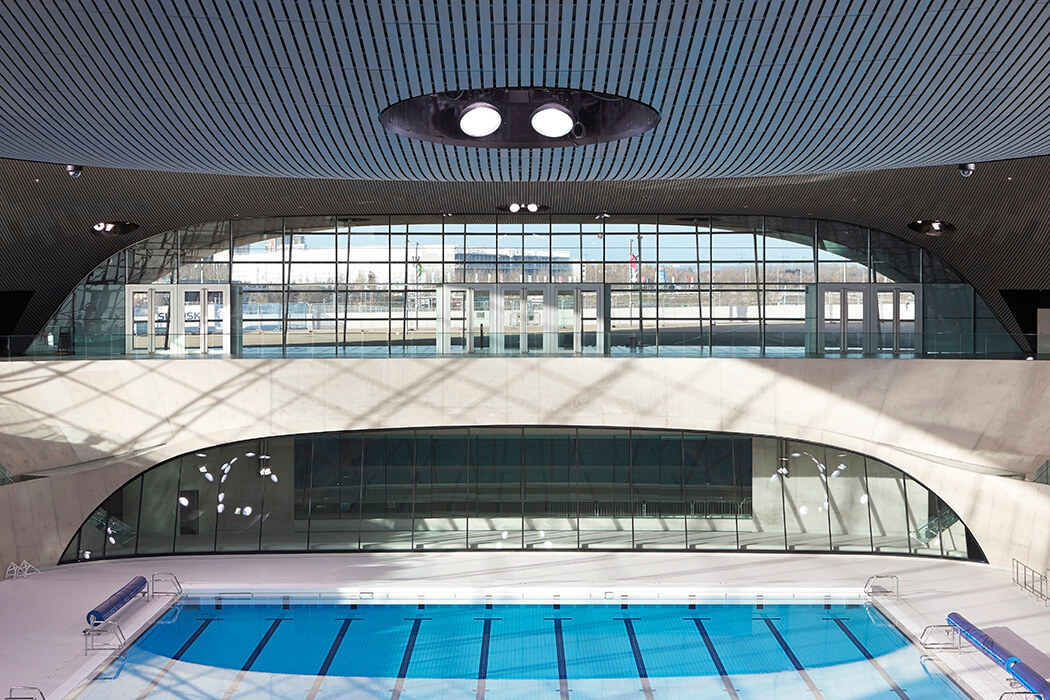 The undualting roof and the large glass façades of the water sports centre Aquatics centre really grab the attention.