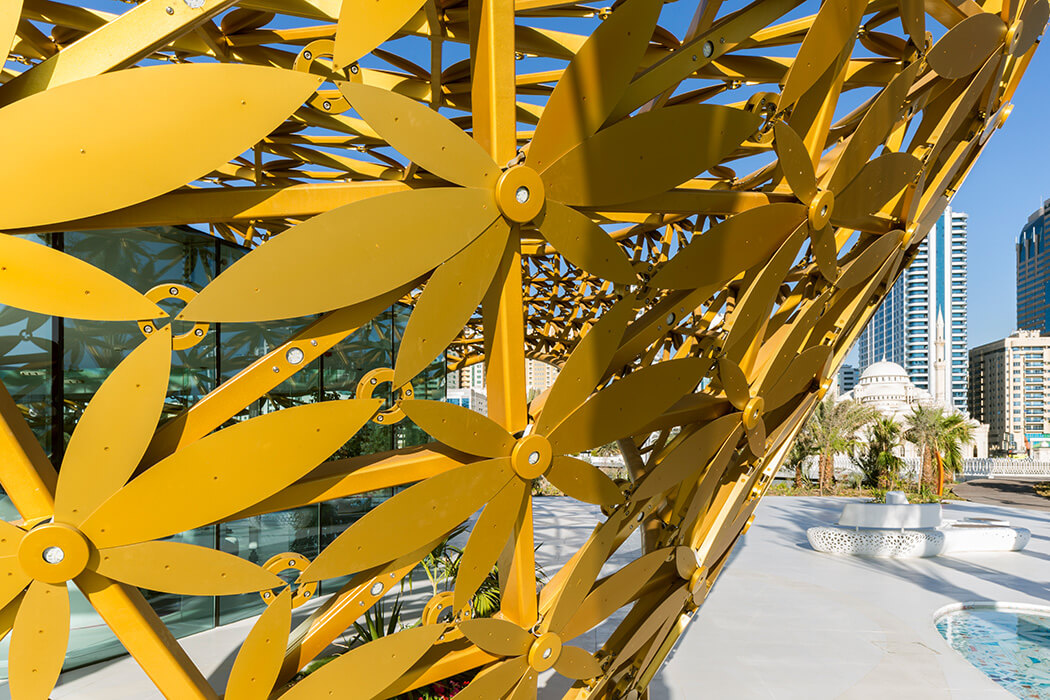 In this construction a triangular lattice of welded steel sections allow plenty of daylight, a golden flower is decorating each node.