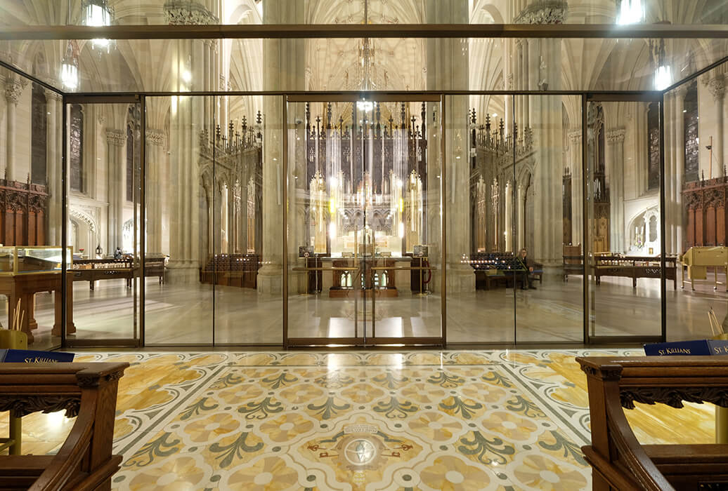 The double leaf glass swing doors in the lower section of the façade are set slightly further forwards in order to preserve the chapel's original mosaic floor.